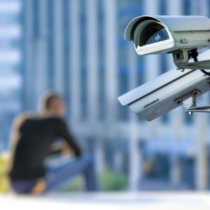 security CCTV camera or surveillance system with young man on blurry background
